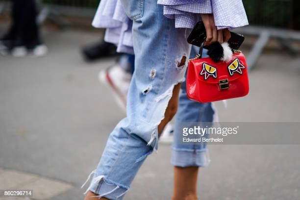 A guest wears ripped blue jeans a red bag with yellow eyes design outside Lanvin during Paris Fashion Week Womenswear Spring/Summer 2018 on September...