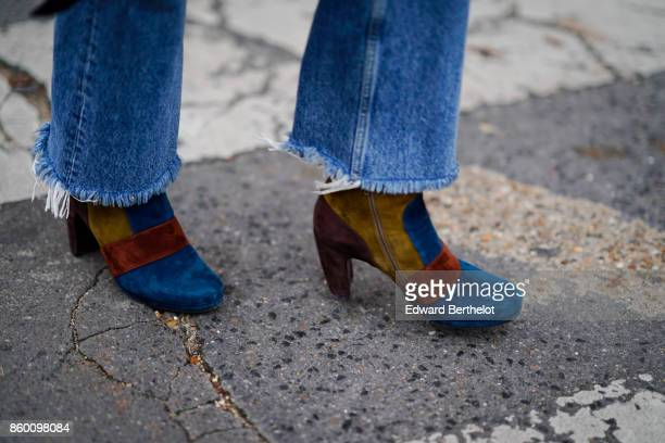 A guest wears ripped blue jeans royal blue suede boots with tawny yellow and brown empiecements outside Lanvin during Paris Fashion Week Womenswear...