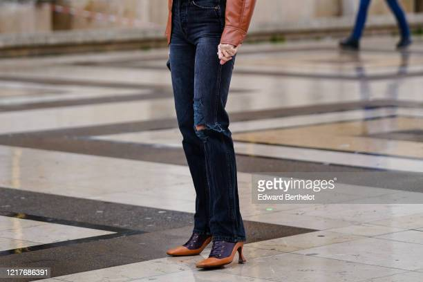 Guest wears ripped denim jeans, brown leather pointy shoes, outside Ann Demeulemeester, during Paris Fashion Week - Womenswear Fall/Winter 2020/2021,...