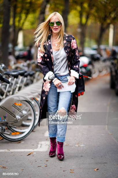 A guest wears ripped jeans red shoes a flower print kimono jacket a gray top outside the Rochas show during Paris Fashion Week Womenswear...