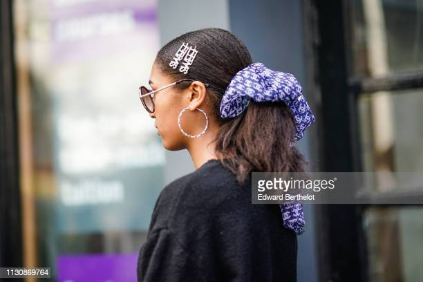 A guest wears round sunglasses large earrings hair clips a purple scarf with the white Chanel logo design during London Fashion Week February 2019 on...