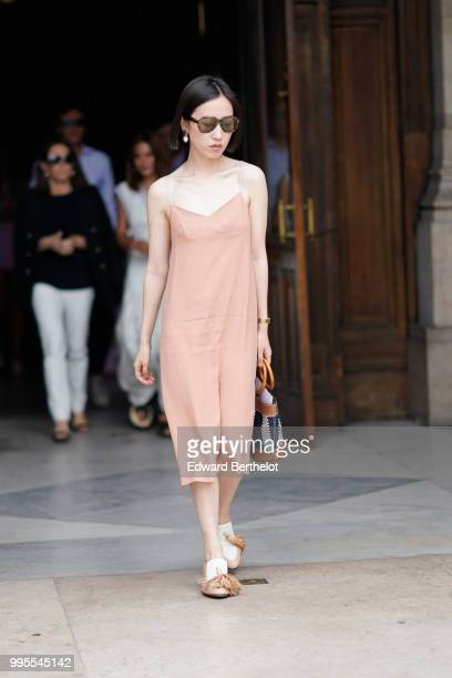 Guest wears salmon colored dress, shoes, white earrings , outside Schiaparelli, during Paris Fashion Week Haute Couture Fall Winter 2018/2019, on...
