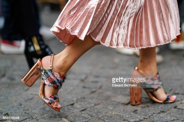 A guest wears shoes with embroidered flowers outside Koche during Paris Fashion Week Womenswear Spring/Summer 2018 on September 26 2017 in Paris...