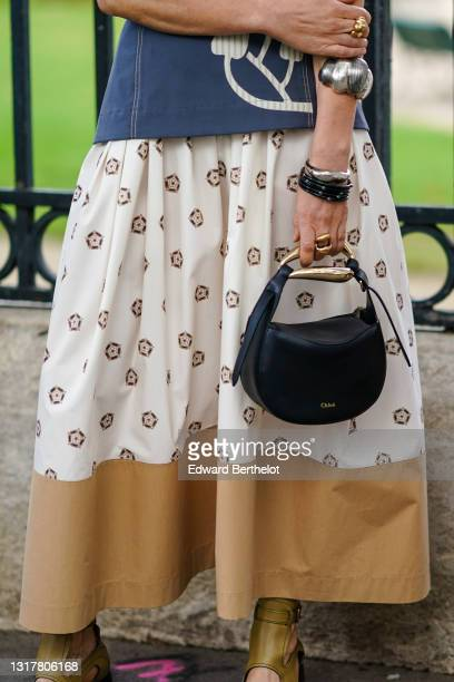 Guest wears silver bracelets, black shiny bracelet, a gold ring, a long white with brown print skirt with a large brown stripe at the bottom, a black...