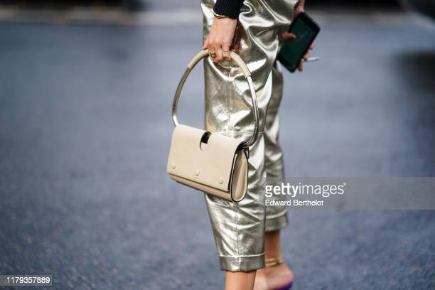 Guest wears silver cropped pants, a bag with a metallic handle, outside Miu Miu, during Paris Fashion Week - Womenswear Spring Summer 2020, on...