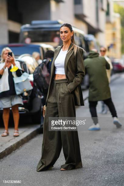Guest wears silver earrings, a white cropped t-shirt, a dark green long blazer jacket, matching dark green palazzo flared suit pants, a brown shiny...