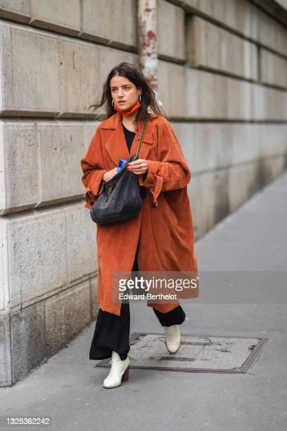 Guest wears silver earrings, an orange ribbed long oversized velvet coat, a black t-shirt, black flared pants, a black suede crossbody bag, gold...