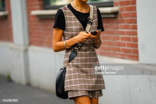 Guest wears silver earrings, necklaces, a black t-shirt, a black / brown / beige / pale pink checkered print pattern V-neck long dress, matching...
