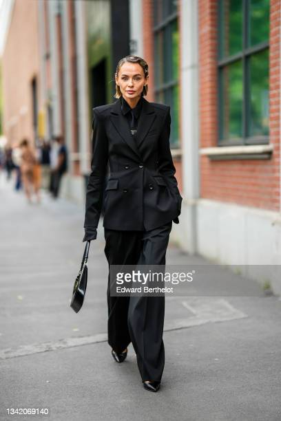 Guest wears silver hair clips, silver and rhinestones earrings, a black shirt, a black tie, a black long blazer jacket, black flared suit pants, a...