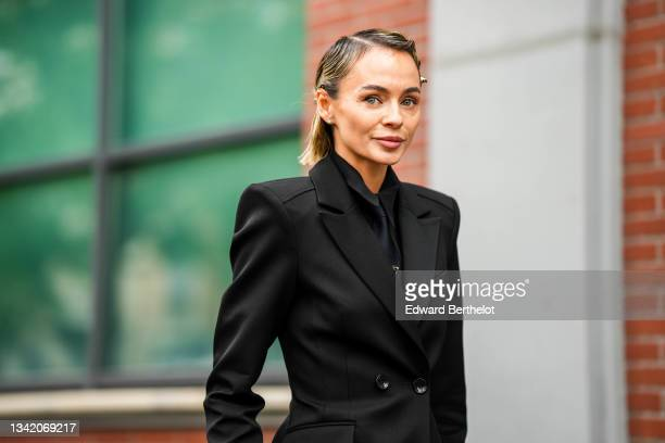 Guest wears silver hair clips, silver and rhinestones earrings, a black shirt, a black tie, a black long blazer jacket, outside the Fendi fashion...