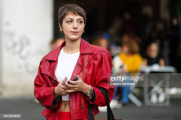 Guest wears silver rings, a white ribbed cropped t-shirt, a red shiny leather oversized biker jacket, red high waist pants, a black large nylon gab...