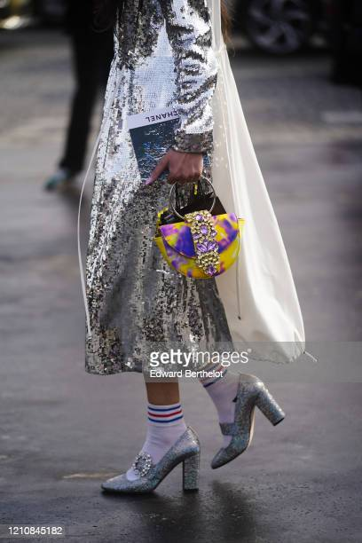 Guest wears silver sequined shiny dress, a bejeweled bag, striped socks, silver bejeweled shoes, outside Chanel, during Paris Fashion Week -...