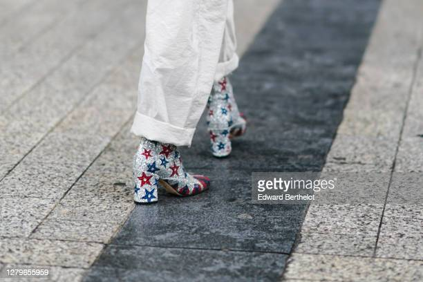 A guest wears silver shiny glittering shoes with printed red and blue stripes outside Miu Miu during Paris Fashion Week Womenswear Spring Summer 2021...