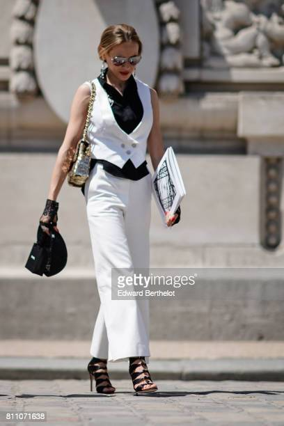 A guest wears silver sunglasses a black shirt a white button low v neck top white flare pants a gold bag black gladiator shoes outside the Chanel...