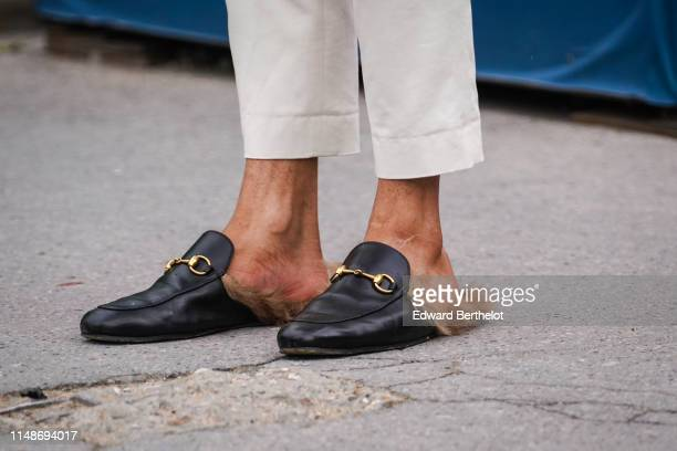 Guest wears slippers shoes with brown fur, outside the Chanel Cruise Collection 2020 At Grand Palais on May 03, 2019 in Paris, France.