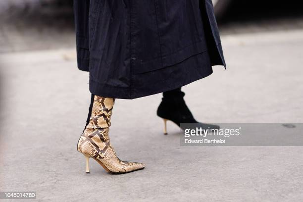 A guest wears snake print boots outside Chanel during Paris Fashion Week Womenswear Spring/Summer 2019 on October 2 2018 in Paris France