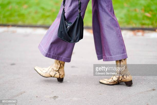A guest wears snake print boots outside Manish Arora during Paris Fashion Week Womenswear Spring/Summer 2018 on September 28 2017 in Paris France