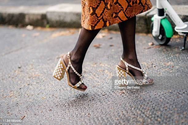 A guest wears strass studded sandals outside Miu Miu during Paris Fashion Week Womenswear Fall/Winter 2019/2020 on March 05 2019 in Paris France