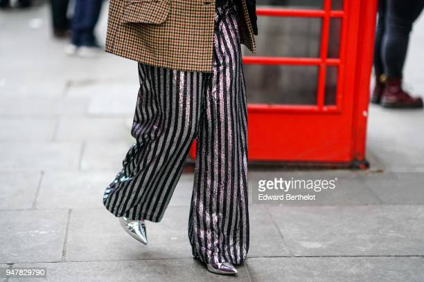 A guest wears striped flare pants during London Fashion Week Men's January 2018 at on January 6 2018 in London England