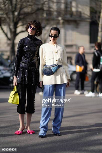 A guest wears sunglasses a balck shiny glitter jacket black cropped flare pants a yellow bag pink shoes a guest wears a white jacket a belt bag blue...