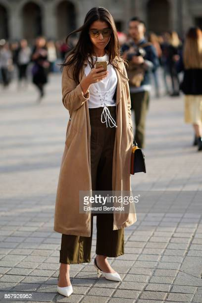 A guest wears sunglasses a beige coat a white top cropped pants white heels outside Louis Vuitton during Paris Fashion Week Womenswear Spring/Summer...