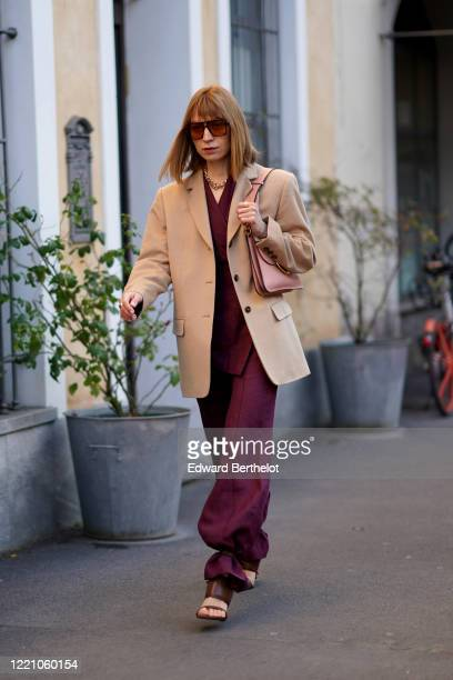 Guest wears sunglasses, a beige jacket, a pink bag, purple pants, a golden necklace, outside Tod's, during Milan Fashion Week Fall/Winter 2020-2021...