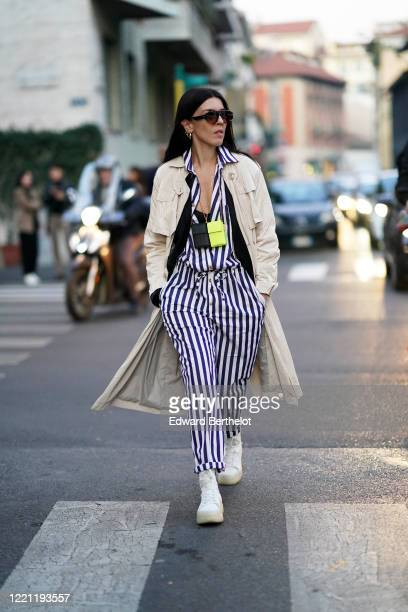 Guest wears sunglasses, a beige long coat, a black and white striped shirt, pants, white sneakers, outside N°21, during Milan Fashion Week...