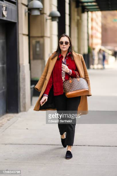 A guest wears sunglasses a beige long coat a Vuitton monogram bag a red jacket black pants shoes during New York Fashion Week Fall Winter 2020 on...