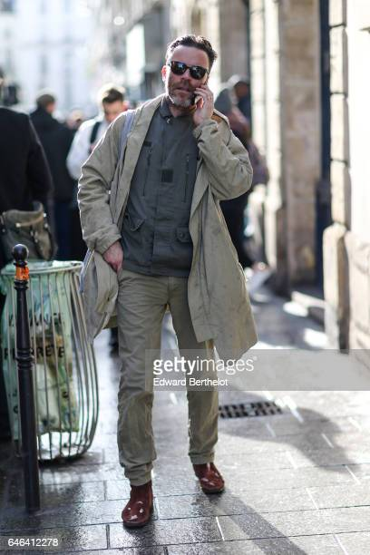 A guest wears sunglasses a beige long jacket a gray coat beige pants and brown shoes outside the AALTO show during Paris Fashion Week Womenswear...