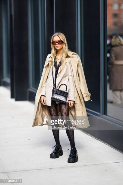 Guest wears sunglasses, a beige long trench coat, a jacket / dress, a black leather crocodile pattern bag, Gucci monogram tights, black leather...