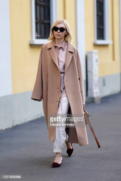 Guest wears sunglasses, a beige long wool coat, a brown leather bag, sandals, outside Tod's, during Milan Fashion Week Fall/Winter 2020-2021 on...