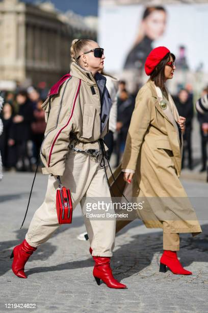 Guest wears sunglasses, a beige oversized leather jacket with purple lines, a red bag, earrings, gray pants, red leather pointy shoes, outside Dior,...