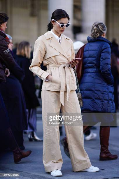 A guest wears sunglasses a beige pantsuit with a safari jacket and wide leg pants white shoes during Paris Fashion Week Womenswear Fall/Winter...