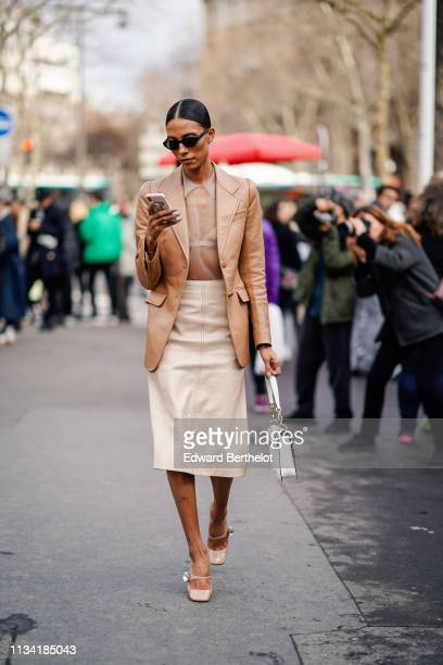 A guest wears sunglasses a beige see through muslin top a camel leather jacket a beige leather skirt a Miu Miu white studded bag beige shoes outside...