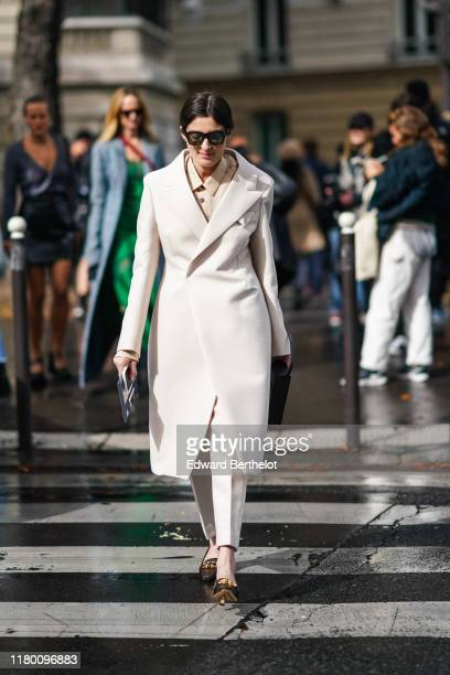 Guest wears sunglasses, a beige shirt, a cream-color wool coat, a dark brown bag, cream-color pants, brown heeled moccasins, outside Miu Miu, during...