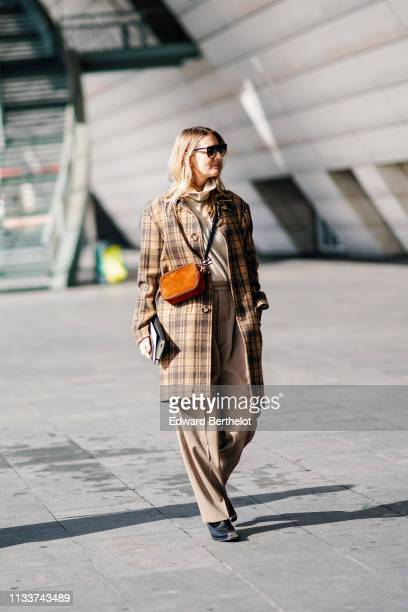 Guest wears sunglasses, a beige turtleneck, a brown checkered coat, a gold leather bag, camel pants, black boots, outside Giambattista Valli, during...