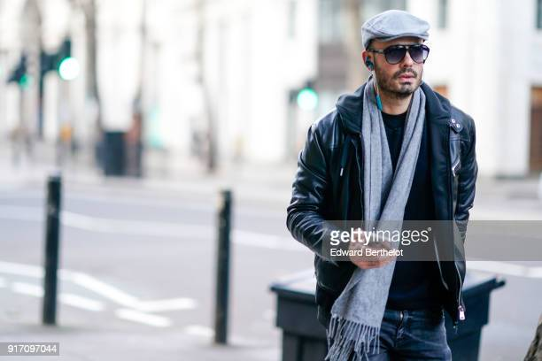 A guest wears sunglasses a beret hat a black leather jacket a scarf during London Fashion Week Men's January 2018 at on January 6 2018 in London...