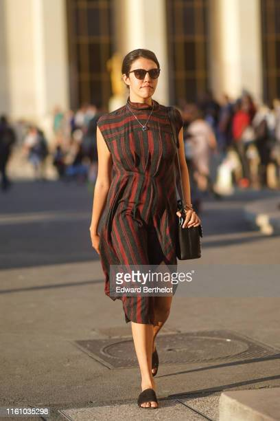 A guest wears sunglasses a black and burgundy hineck striped frontsplit dress a black bag black flat mules outside Azzaro during Paris Fashion Week...