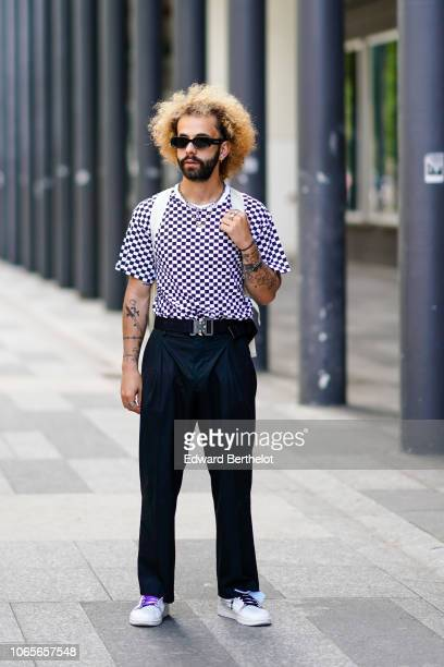 A guest wears sunglasses a black and white checked tshirt black flared pants white sneakers shoes outside Issey Miyake during Paris Fashion Week...