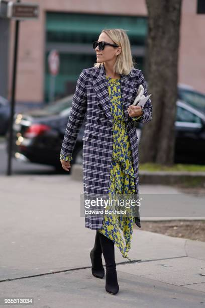 A guest wears sunglasses a black and white checkered coat a flowy blueprint yellow pleated layerdress black highheeled pointy toe boots during Paris...