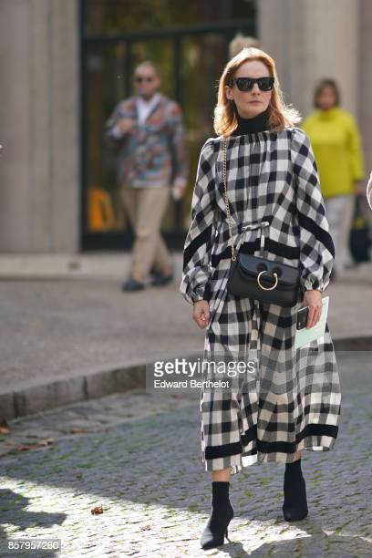 A guest wears sunglasses a black and white gingham dress a black JW anderson bag black shoes outside Miu Miu during Paris Fashion Week Womenswear...