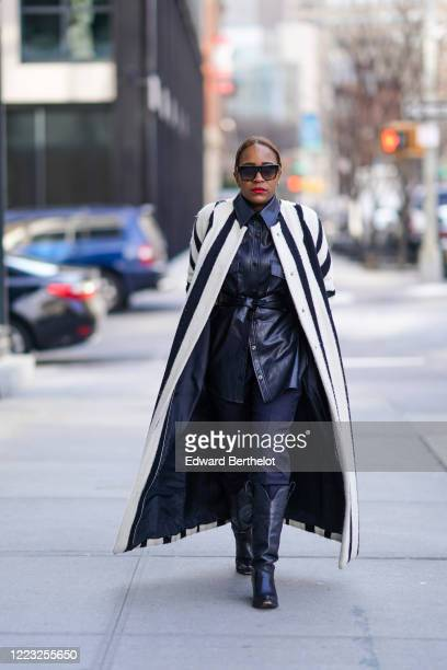Guest wears sunglasses, a black and white striped long coat / cape, a black leather jacket, black pants, leather cowboy boots, during New York...