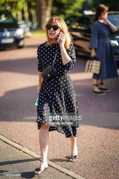 Guest wears sunglasses, a black bag, a black dress with white polka dots, black sandals with bow, outside Miu Miu Club 2020, on June 29, 2019 in...