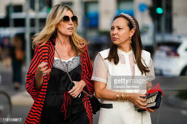 A guest wears sunglasses a black bag a red jacket with black stripes a black dress decorated with black lace A guest wears a pearl embellished brown...