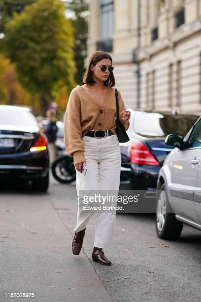 A guest wears sunglasses a black bag with polka dots a camel Vneck cardigan a black belt white pants brown crocodile pattern boots outside Elie Saab...