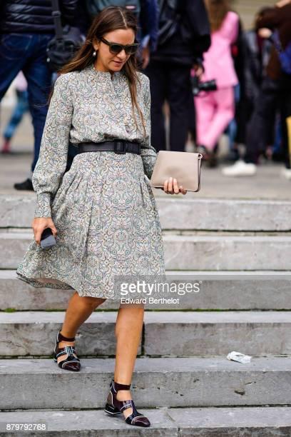A guest wears sunglasses a black belt a dress black sandals a clutch holds a smartphone outside Margiela during Paris Fashion Week Womenswear...