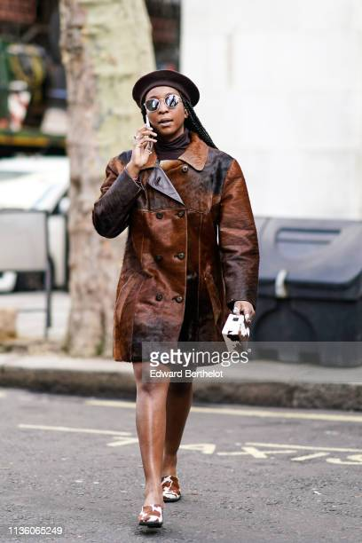 A guest wears sunglasses a black beret a brown turtleneck a brown doublebreasted cowhide coat cowhide pattern mules a mini cowhide pattern bag during...