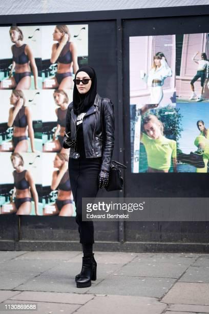 Guest wears sunglasses, a black biker jacket, a black skirt, black platform ankle boots, studded black gloves, during London Fashion Week February...
