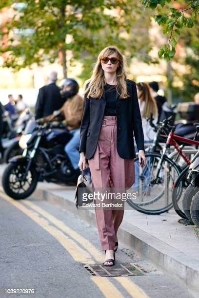 A guest wears sunglasses a black blazer jacket pink pants during London Fashion Week September 2018 on September 17 2018 in London England