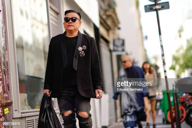 A guest wears sunglasses a black blazer jacket ripped jeans outside Yohji Yamamoto during Paris Fashion Week Menswear SpringSummer 2019 on June 21...